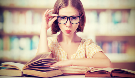 funny crazy  girl student with glasses reading books in the library Banco de Imagens