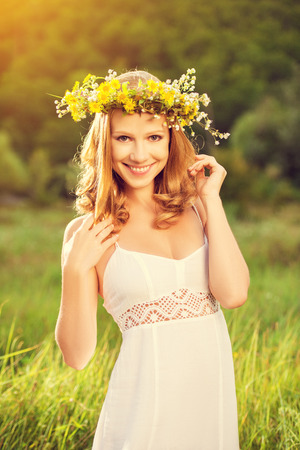 young beautiful woman in wreath of flowers  in the green grass outdoors in nature photo