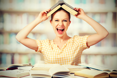 frantic: funny mad  girl student with glasses shouts with books in the library Stock Photo