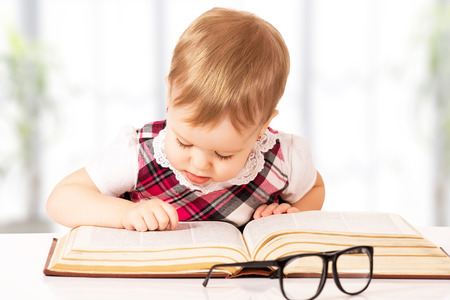 Happy funny baby girl in glasses reading a book in a library Stock Photo