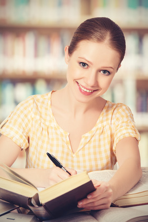 happy student girl learning: writing, reading books photo