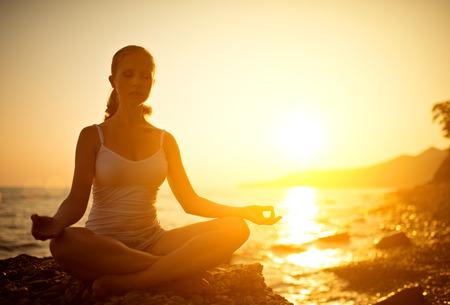 mujer meditando: yoga en la playa. mujer meditando en posici�n de loto en la playa al atardecer
