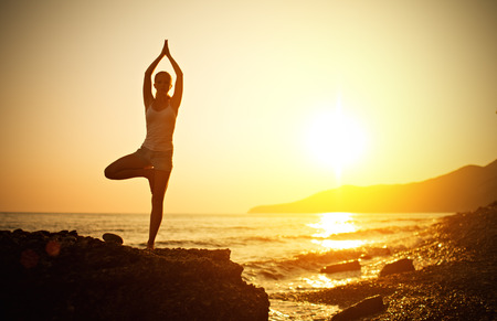 woman doing yoga on the beach by the sea at sunset photo