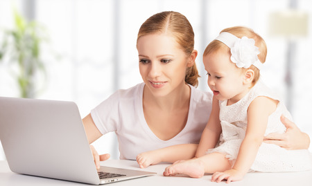 young leave: happy family mother and baby at home using laptop computer Stock Photo