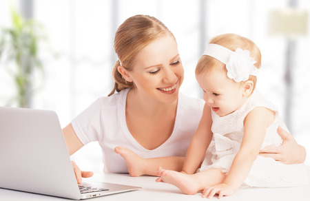 happy family mother and baby at home using laptop computer photo