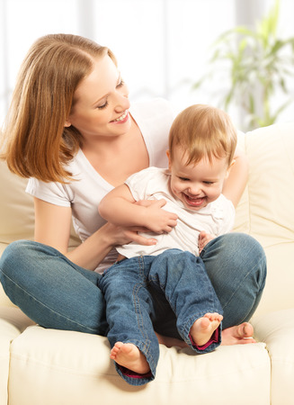 small children: happy family. Mother and baby daughter at home on the sofa at home Stock Photo