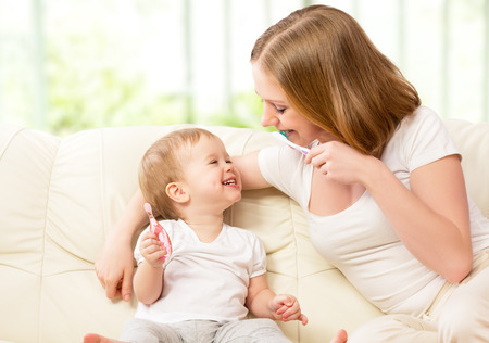 tooth brush: happy family and health. mother and daughter baby girl brushing their teeth together Stock Photo