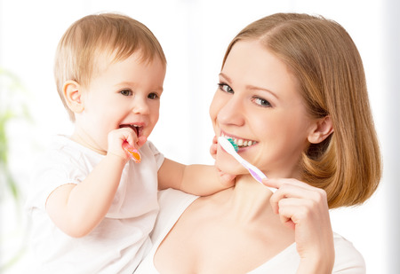 toothpaste: happy family and health. mother and daughter baby girl brushing their teeth together Stock Photo