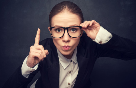 strict: Funny strict teacher with glasses shakes his finger at the school board Stock Photo