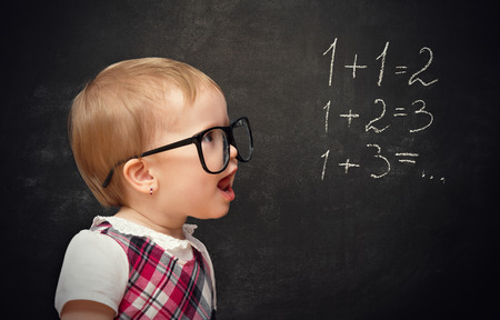 examples: Funny baby girl pupil solves arithmetic examples on blackboard Stock Photo