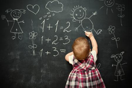 赤ちゃんの女の子の生徒が黒板にチョークを描画します 写真素材