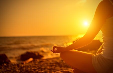 de hand van een vrouw mediteren in een yoga pose op het strand bij zonsondergang Stockfoto