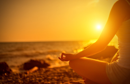 meditating woman: hand of a woman meditating in a yoga pose on the beach at sunset Stock Photo