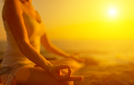 positions: hand of a woman meditating in a yoga pose on the beach at sunset Stock Photo