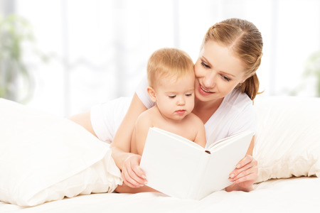 Mother reading a book the baby in bed before going to sleep Banco de Imagens