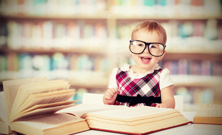 funny baby girl in glasses reading a book in a library photo