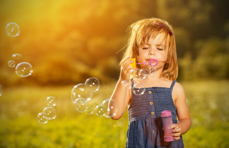 little girl blowing soap bubbles in summer in nature