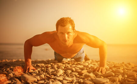 man athlete trains, practicing, playing sports pushed on the nature on the beach photo