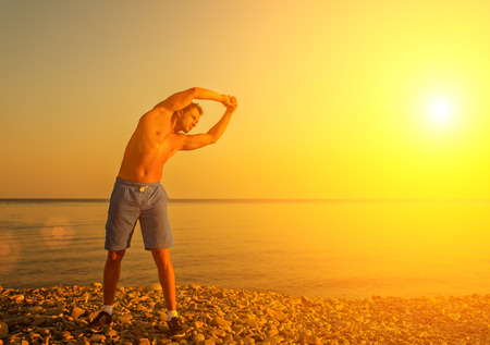 man athlete practicing, playing sports and yoga on the beach at sunset photo