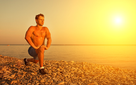 yoga sunset: man athlete practicing, playing sports and yoga on the beach at sunset Stock Photo