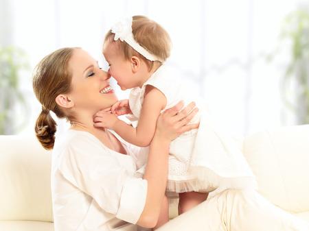 mama e hija: familia feliz. Madre y beb� juegos de la hija, abrazos, besos en casa en el sof�