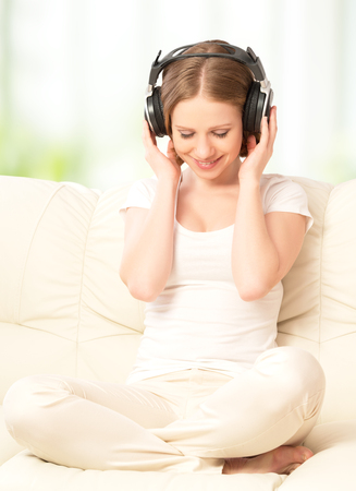 beautiful girl in headphones enjoying music at home on the couch Stock Photo - 27155681