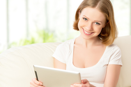 happy woman with tablet pc  on the sofa at home Stock Photo - 27155695