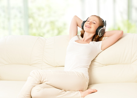 beautiful girl in headphones enjoying music at home on the couch Stock Photo - 27155704