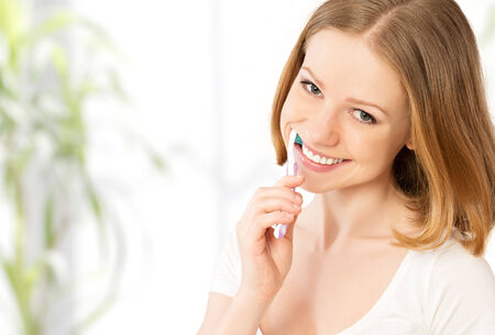 Healthy happy young woman with snow-white smile brushing her teeth with a toothbrush Stock Photo - 27155737