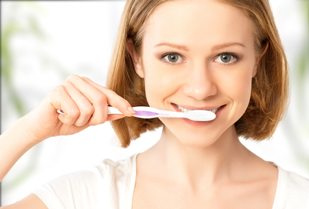 Healthy happy young woman with snow-white smile brushing her teeth with a toothbrush Stock Photo