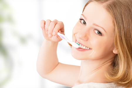 Healthy happy young woman with snow-white smile brushing her teeth with a toothbrush Stock Photo - 27155768