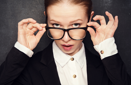 Surprised funny teacher in glasses shouts at the school board Stock Photo