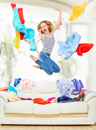 Funny happy girl with flying clothes jumping at home photo