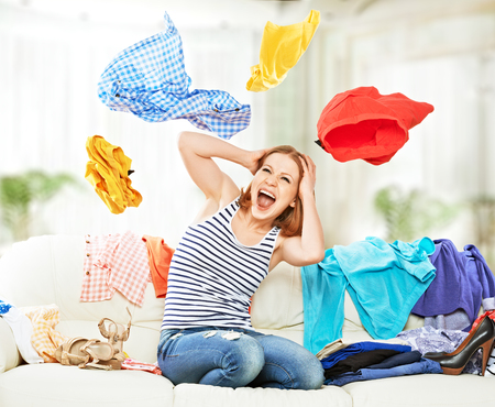 Funny happy girl with flying clothes on the sofa at home photo