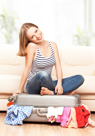 packing suitcase: happy woman is packing a suitcase at home