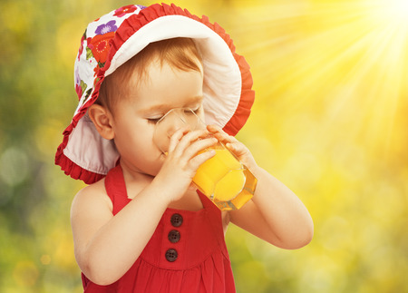 health drink: baby girl drinking orange juice in the summer outdoors Stock Photo
