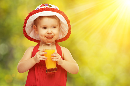fruit drinks: baby girl drinking orange juice in the summer outdoors Stock Photo