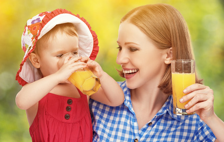 family mother and baby daughter drinking orange juice in the summer outdoors photo