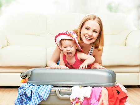 packing: Mother and baby girl with suitcase baggage and clothes ready for traveling on vacation