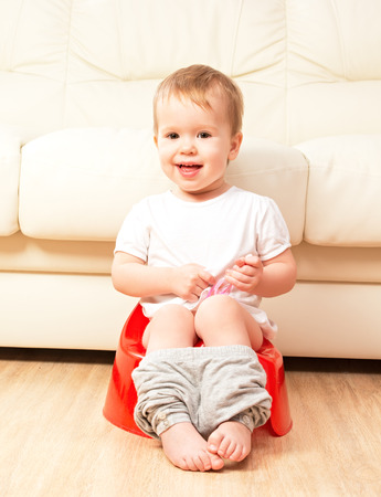 baby wardrobe: baby sitting on the potty in the toilet