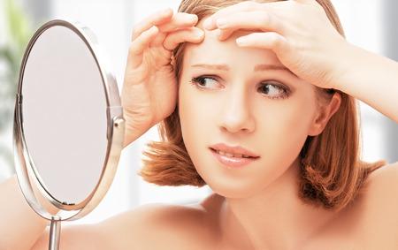 Joven y bella mujer sana asustó sierra en el acné espejo y arrugas Foto de archivo - 27323348