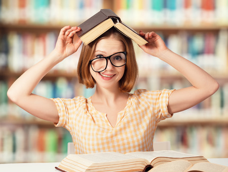 crazy girl: tired funny crazy  girl student with glasses reading books in the library