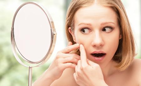 jonge mooie gezonde vrouw bang in de spiegel zag acne en rimpels Stockfoto