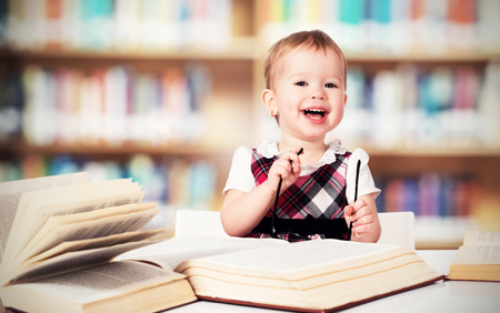 Happy funny baby girl in glasses reading a book in a library photo