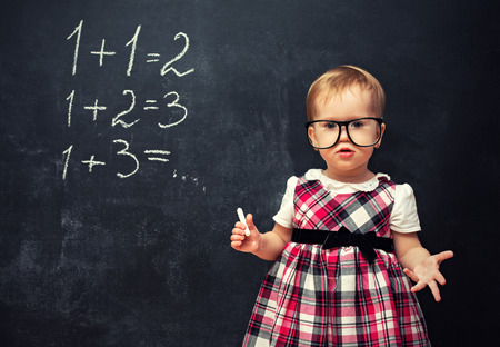arithmetic: baby girl pupil in glasses and chalk at a school board with arithmetic examples