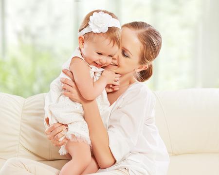 bebes lindos: familia feliz. Madre y bebé juegos de la hija, abrazos, besos en casa en el sofá