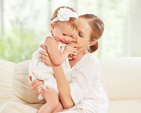 cute babies: happy family. Mother and baby daughter plays, hugging, kissing at home on the sofa