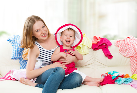 Happy Mother and baby girl with clothes ready for traveling on vacation photo
