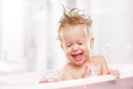 gelukkig grappige baby lachen en badend in het bad
