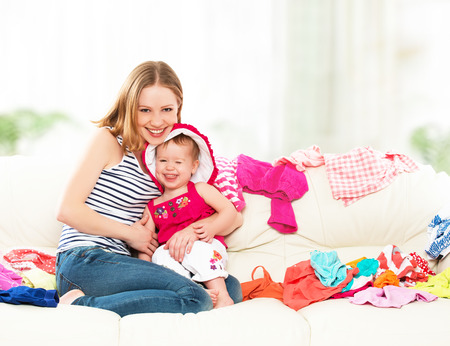 dowry: Happy Mother and baby girl with clothes ready for traveling on vacation